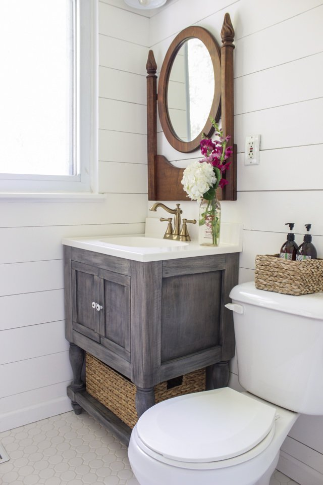 The finish on this is a weathered grey, and we love the styling of this whole room. Try your hand at a DIY bathroom remodeling idea like this one!